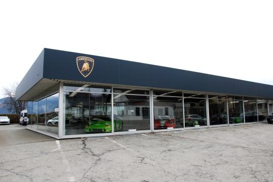 Von außen sieht das Gebäude aus wie ein Lamborghini Handel. Beim näheren Betrachten fällt auf: Das Grüne im Schaufenster ist kein Straßenfahrzeug, sondern ein Rennbolide. (Foto: Jennifer Falkner / Jensationel Motorsport Media)